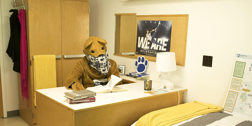 Nittany Lion masked and studying in a student room